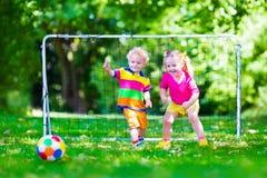 踢橄榄球的孩子在校园 免版税库存图片