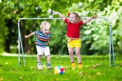 踢橄榄球的孩子在校园 免版税库存照片