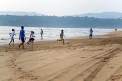 踢橄榄球的孩子在Agonda海滩在果阿,印度 免版税库存照片