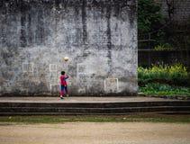 踢橄榄球的孩子对墙壁 免版税库存图片