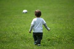 踢橄榄球的小孩 免版税图库摄影