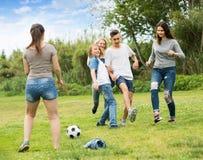 踢橄榄球的少年在公园 免版税图库摄影