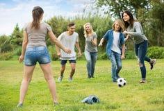 踢橄榄球的少年在公园 免版税库存图片