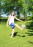 踢橄榄球的少年 免版税图库摄影