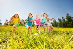 踢橄榄球的愉快的孩子在黄色草甸 免版税库存照片