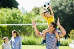 踢橄榄球的愉快的家庭在公园 免版税图库摄影