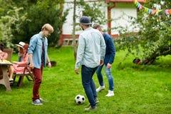 踢橄榄球的愉快的朋友在夏天庭院 免版税库存图片