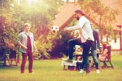 踢橄榄球的愉快的朋友在夏天庭院 库存照片