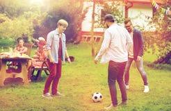 踢橄榄球的愉快的朋友在夏天庭院 免版税库存照片