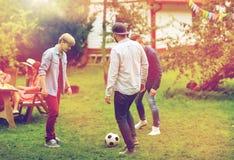 踢橄榄球的愉快的朋友在夏天庭院 免版税图库摄影