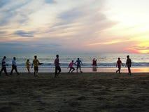 踢橄榄球的本机在海滩 库存图片
