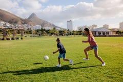 踢橄榄球的母亲和儿子在公园 库存图片