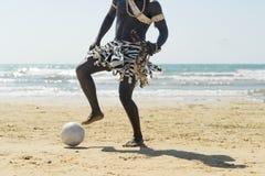 踢橄榄球的海滩的黑人 免版税库存照片