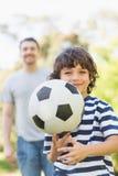 踢橄榄球的父亲和儿子在公园 图库摄影