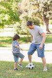 踢橄榄球的父亲和儿子在公园 库存图片