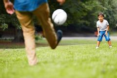 踢橄榄球的父亲和儿子在公园 免版税库存图片