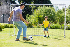 踢橄榄球的父亲和儿子在公园 库存照片