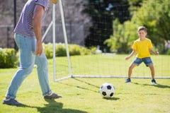 踢橄榄球的父亲和儿子在公园 免版税库存照片