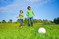 踢橄榄球的父亲和孩子在公园 库存图片