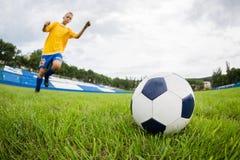 踢橄榄球的男孩在体育场。 免版税库存照片