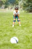 踢橄榄球的男孩在公园 免版税库存图片