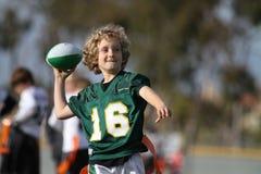 踢橄榄球的男孩 库存照片