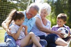 踢橄榄球的祖父母和孙在庭院里 免版税库存照片