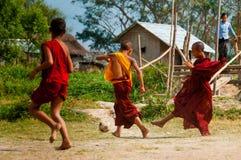 踢橄榄球的红色长袍的三名修士 图库摄影