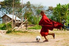 踢橄榄球的红色长袍的修士 库存图片