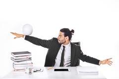 踢橄榄球的被集中的商人 免版税库存图片