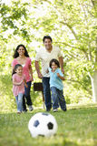 踢橄榄球的年轻西班牙家庭在公园 免版税图库摄影