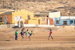 踢橄榄球足球的当地青年人在乡操场在纳米比亚 库存图片