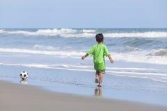 踢橄榄球足球的男孩儿童连续海滩 免版税库存照片