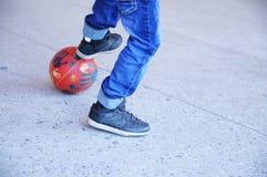 踢橄榄球,少年有一个球的` s腿的男孩在沥青,足球队员球员,训练室外,活跃生活方式 免版税库存图片