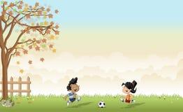 踢橄榄球/足球的男孩和女孩 免版税图库摄影