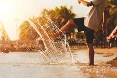 踢海水表面上的一个坚强的男孩与他的做飞溅的腿的在海滩 免版税库存照片