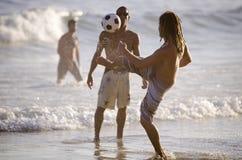踢海滩橄榄球的年轻巴西人 库存图片