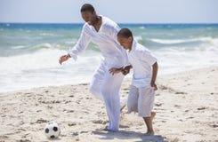 踢海滩橄榄球足球的非裔美国人的父亲儿子 库存照片