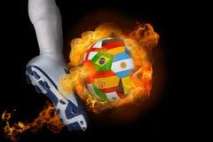 踢火焰状国际旗子球的足球运动员 免版税库存照片