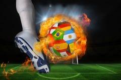 踢火焰状国际旗子球的足球运动员 库存照片