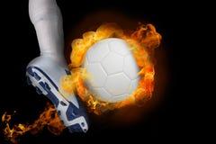 踢火焰状球的足球运动员 免版税库存照片