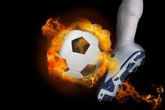 踢火焰状球的足球运动员 库存照片