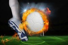 踢火焰状球的足球运动员 免版税库存图片