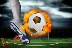 踢火焰状球的足球运动员 免版税图库摄影