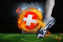 踢火焰状瑞士旗子球的足球运动员 库存图片
