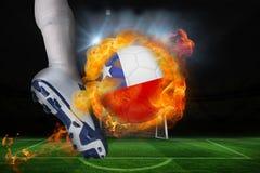 踢火焰状辣椒旗子球的足球运动员 免版税图库摄影