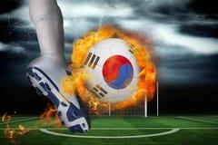 踢火焰状韩国旗子球的足球运动员 免版税库存图片