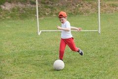 踢球的小男孩在公园 踢足球橄榄球在公园 锻炼和活动的体育 免版税库存图片