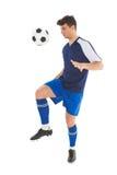 踢球的蓝色球衣的足球运动员 图库摄影