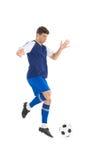 踢球的蓝色球衣的足球运动员 库存图片